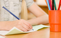 Hand with pencil writing in a notebook.  Royalty Free Stock Photos