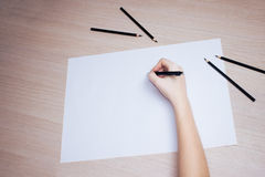 Hand with pencil writing on white paper sheet Royalty Free Stock Images