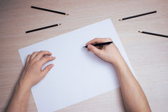 Hand with pencil writing on white paper sheet Stock Photo