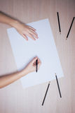 Hand with pencil writing on white paper sheet Stock Image