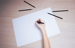 Hand with pencil writing on white paper sheet Stock Photos