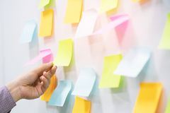 Hand people business man  notes pad in the wall at meeting room. Sticky post it note paper reminder schedule board. Close up hand people business man  notes pad royalty free stock image