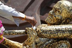 Hand of people gild to Buddha statue gold covered thinly with go. Ld stock images