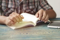 Hand of people, student opening  and reading text book on wood table with copy space, in library, concept as education attempt and. Make effort to win, intend Stock Image