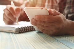 Hand of people, student writing,  note on notebook and looking phone  on wood table with copy space, in library, concept as educat. Ion and make effort to win Stock Image