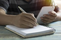 Hand of people, student writing, note on notebook and looking phone on wood table with copy space, in library, concept as educat. Ion and make effort to win Royalty Free Stock Photography