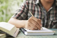 Hand of people, student writing and note on notebook on wood table with copy space, in library, concept as education attempt and m. Ake effort to win, intend to Stock Photography
