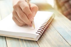 Hand of people, student writing and note on notebook on wood table with copy space, in library, concept as education attempt and m. Ake effort to win, intend to Royalty Free Stock Photos