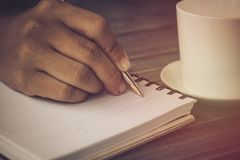 Hand of people, student writing and note on notebook on wood table with copy space, in library, concept as education attempt and m. Ake effort to win, intend to Royalty Free Stock Photo