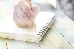 Hand of people, student writing and note on notebook on wood table with copy space, in library. Concept as education attempt and make effort to win, intend to Royalty Free Stock Images