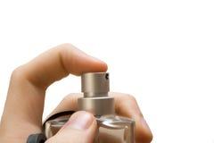 Hand with perfume bottle. Finger pressing the sprayer on perfume bottle Stock Image