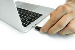 Hand of a person connecting an external hard drive to his laptop, white table. Hand of a person connecting an external hard drive to his laptop on a white table royalty free stock photo