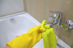 Hand of a man cleans the water tap wearing yellow rubber hygiene gloves. Image stock images