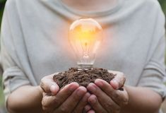Hand of person holding light bulb for idea or success and solar. Energy concept Stock Photo
