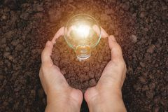 Hand of person holding light bulb with soil for idea, success Royalty Free Stock Photo