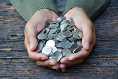 Hand of person holding stack coins on old bark background for sa Stock Image