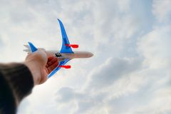 The hand of the person holds the toy plane against the blue sky and white clouds. The concept of freedom, flight and travel stock photos
