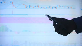 Hand of the person with the phone, typing a text message on the smartphone on the background of the LCD screen with the. Graph, financial market exchange stock video footage