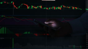 Hand of the person with the phone, typing a text message on the smartphone on the background of the LCD screen with the. Graph, financial market exchange stock footage