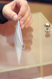 Hand of a person putting a ballot into voting box. Royalty Free Stock Image