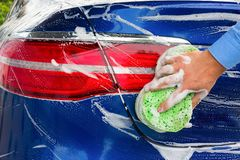 Hand of the person with a sponge, the washing blue car. Close-up stock images