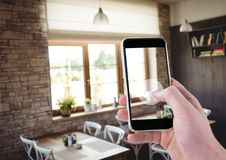 Hand of person taking a picture of a dinning room with her smartphone. Digital composite of Hand of person taking a picture of a dinning room with her smartphone Royalty Free Stock Photo