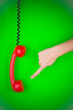 Hand and Phone. Hand pointed at a red telephone receiver Royalty Free Stock Photo
