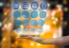 hand with phone with application blue icons panel over. Blurred city at night background Royalty Free Stock Photo