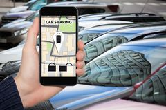 Car sharing concept. Hand with phone on a background of vehicle. Car sharing concept Stock Images