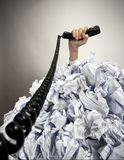 Hand with phone reaches out from heap of papers Royalty Free Stock Photography