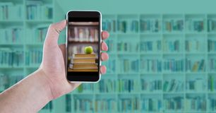 Hand with phone showing book pile with apple against blurry bookshelf with blue overlay Royalty Free Stock Image