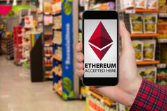 Hand with phone, store on a background. On the screen of the device the inscription `Ethereum accepted here royalty free stock photos
