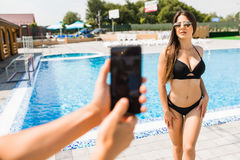 Hand with phone take photo of beauty sexy woman in swimwear near swimming pool. Time for summer photo. Summer time Stock Photo