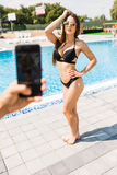 Hand with phone take photo of beauty woman in swimwear near swimming pool. Time for summer photo. Summer time royalty free stock image