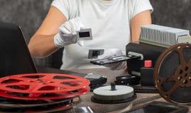 Hand photographer digitize film slide for saving. Close up hand photographer digitize film slide for saving stock photography