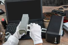 Hand photographer digitize film slide for saving. Close up hand photographer digitize film slide for saving royalty free stock photo