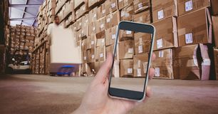 Hand photographing boxes in warehouse. Digital composite of Hand photographing boxes in warehouse Royalty Free Stock Photos
