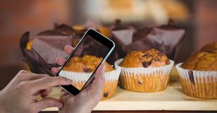 Hand photographing muffins through smart phone at bakery. Digital composite of Hand photographing muffins through smart phone at bakery stock image
