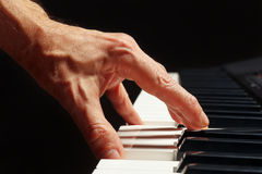 Hand of pianist play the keys of the electronic synth on black background close up Stock Photography
