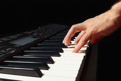 Hand of pianist playing the electronic synth on black background Stock Photo