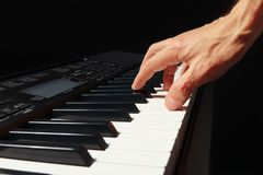 Hand of pianist playing the synth on black background Royalty Free Stock Photos
