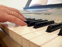 Hand with piano keyboard Stock Photos