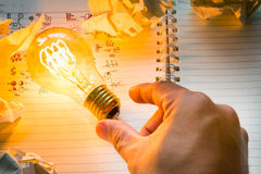 Hand pick light bulb with drawing graph  over  Note book Stock Photos