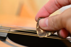 Hand with pick on strings Royalty Free Stock Photos