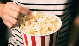 Pop corn. Hand pick up pop corn, junk food concept Stock Photography