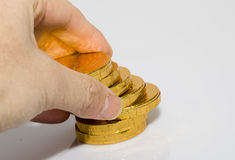 Hand pick up some coins. Hand pick up some yellow coins (made of Chocolate Royalty Free Stock Photography