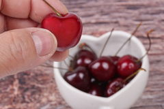 Hand-picked cherriy and cherries in heart-shaped mug on wooden. Royalty Free Stock Photos