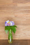 Hand picked flowers in vase on wooden background Stock Photo