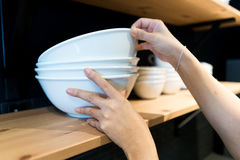 Hand picked a white big bowl on the wooden shelf Stock Photography