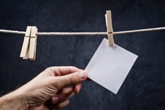 Hand picking Blank note paper attached to rope with clothes pins Royalty Free Stock Image